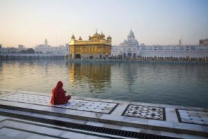 India, Amritsar, Golden Temple, Woman praying against temple