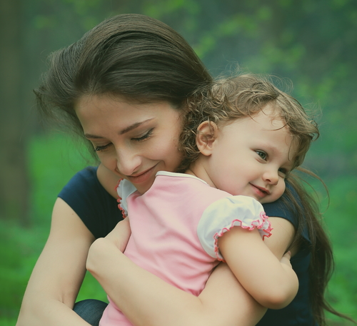 Happy loving mother and girl cuddling outdoor summer background. Closeup tender and love portrait